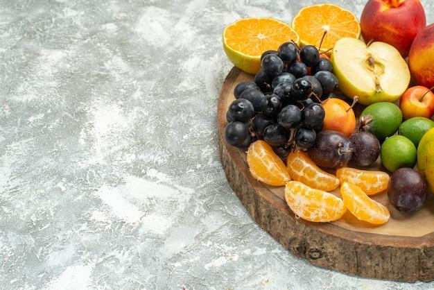 Widok z przodu inny skład owoców pokrojony w plasterki całe świeże owoce na białej przestrzeni