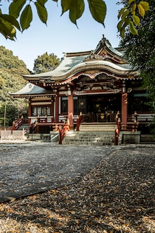 Widok z przodu japońskiej świątyni z jesiennymi liśćmi