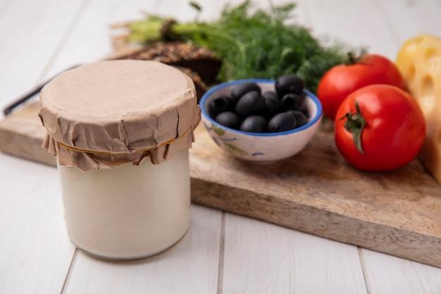 Widok z przodu jogurt w słoiku z oliwkami pomidory kromki ciemnego chleba i koperku na statywie na białym tle