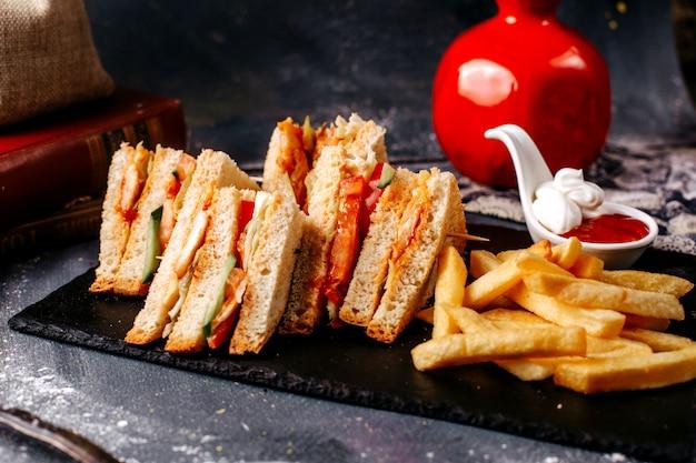 Widok z przodu kanapki smaczne w plasterkach z frytkami na szarym biurku