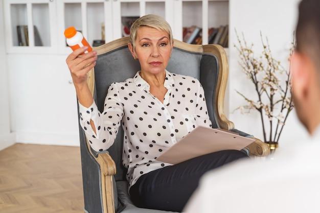 Widok z przodu kaukaskiej lekarki trzymającej w ręku butelkę tabletek