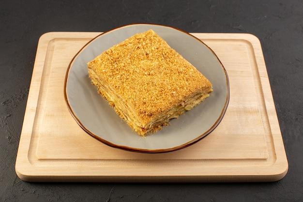 Widok z przodu kawałek ciasta pyszne i pieczone wewnątrz płyty na drewnianym biurku i ciemne ciasto biszkoptowe słodkie