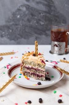 Widok z przodu kawałka ciasta wewnątrz talerza z herbatą przy świecach i małymi gwiazdkami na jasnej powierzchni