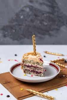 Widok z przodu kawałka ciasta wewnątrz talerza ze świecami na lekkim biurku