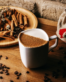 Widok z przodu kawy wraz z nasionami cynamonu i kawy na brązowej podłodze