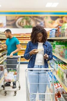 Widok z przodu klientów chodzących w przejściu z wózkami sklepowymi