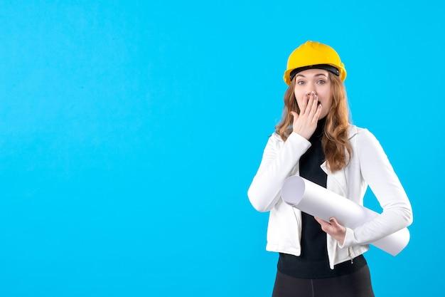 Widok z przodu kobiecego architekta w żółtym kasku trzymającego plan zaskoczony na niebiesko