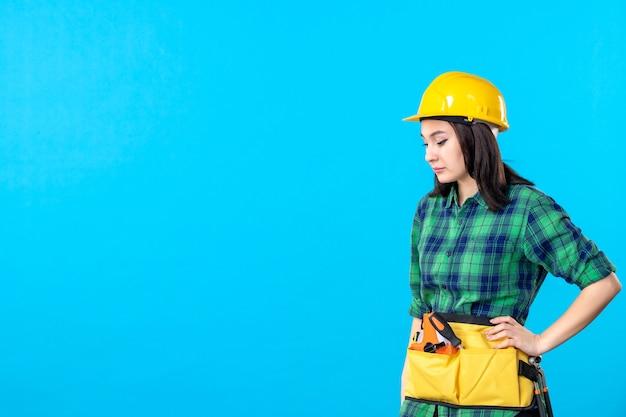 Widok z przodu kobiecego budowniczego w mundurze i kasku na niebiesko
