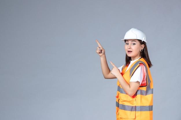 Widok z przodu kobiecego budowniczego w mundurze na białej ścianie