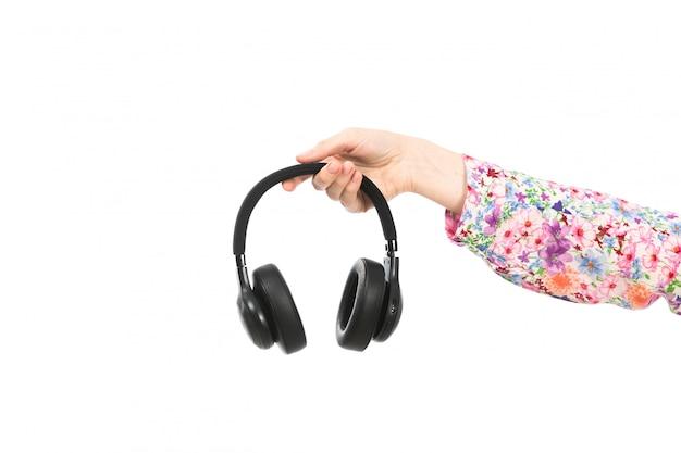 Widok z przodu kobiecej dłoni trzymającej czarne słuchawki na białym