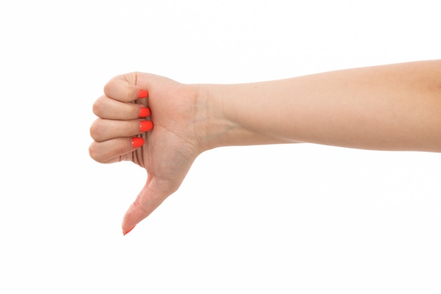 Widok z przodu kobiecej dłoni z kolorowymi paznokciami w przeciwieństwie do znaku na białym