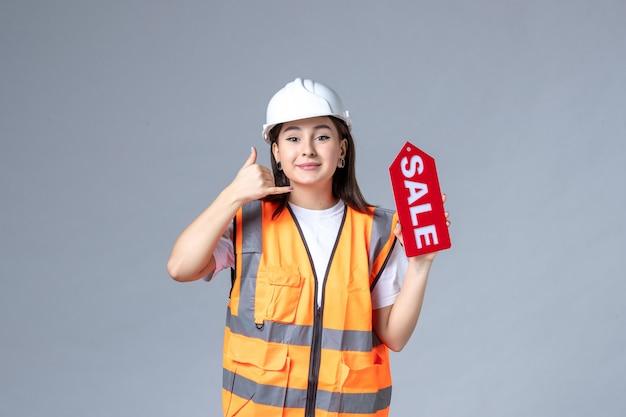 Widok z przodu kobiecej konstruktorki trzymającej czerwoną tablicę sprzedażową na szarej ścianie
