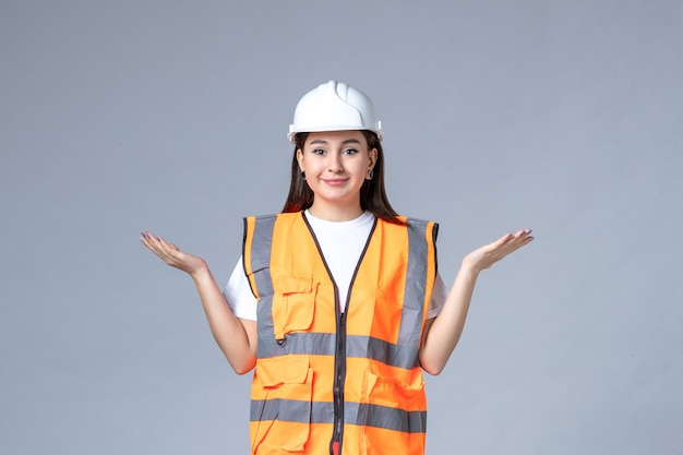 Widok z przodu kobiecej konstruktorki w mundurze i kasku ochronnym na szarej ścianie