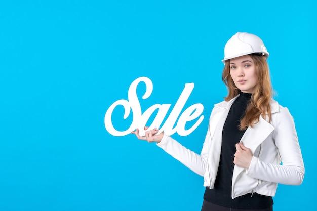 Widok z przodu kobiet architekta trzymającego białą sprzedaż piszącą na niebiesko