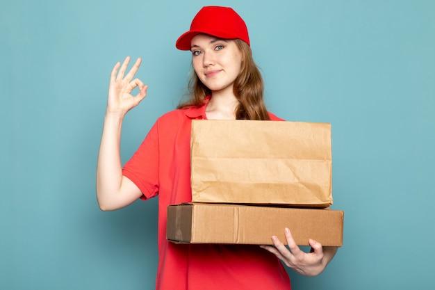 Widok z przodu kobiet atrakcyjny kurier w czerwonej koszulce polo czerwonej czapce gospodarstwa brązowe opakowania uśmiecha się na niebieskim tle usługi gastronomiczne
