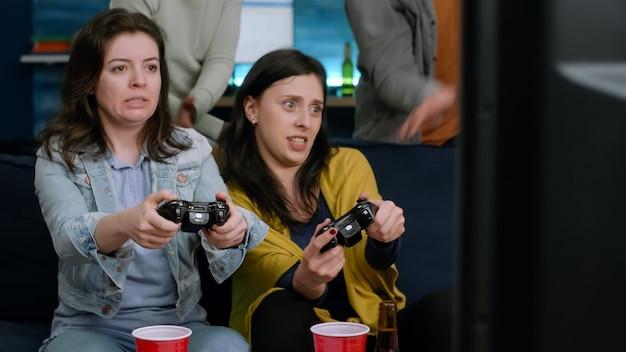 Widok z przodu kobiet grających w gry wideo w telewizji za pomocą kontrolera do gier siedzącego na kanapie późno w nocy w salonie. grupa mieszanych ras bawiących się, towarzysko podczas gry w zawodach