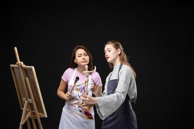 Widok z przodu kobiet malarzy rysujących na sztalugach na czarnej ścianie kolor rysować obrazy praca sztuka zdjęcie artysta obraz