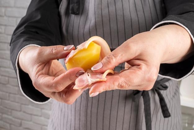 Widok z przodu kobiet szefa kuchni zawijanie boczku wokół owoców