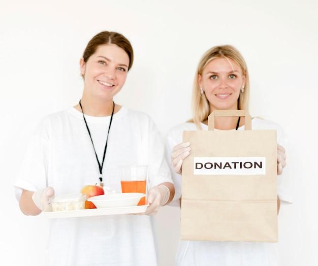 Widok z przodu kobiet trzymających worek darowizny i żywność