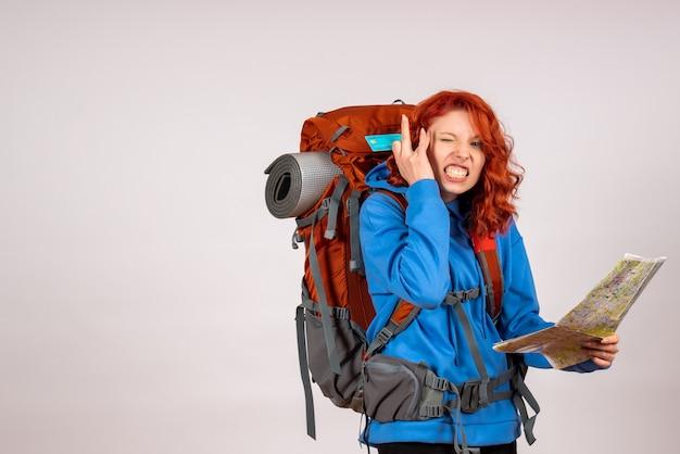 Widok z przodu kobiet turystycznych udających się na wycieczkę w góry z mapą i kartą bankową