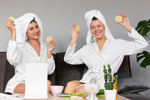 Widok z przodu kobiet w szlafroki i ręczniki trzymając plasterki cytryny