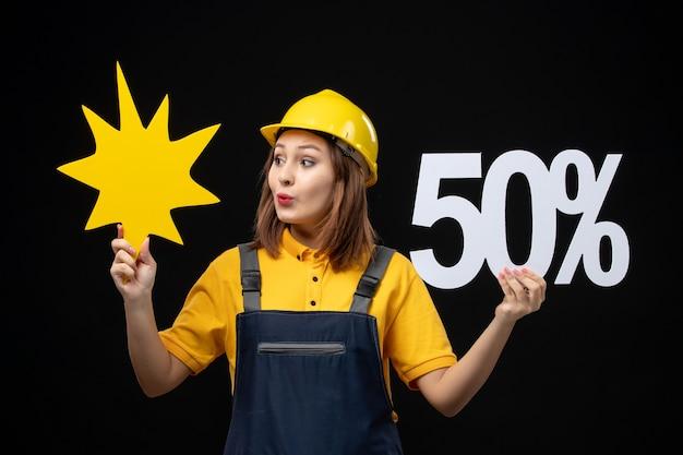 Widok z przodu kobieta budowlana trzymająca żółtą postać i na czarnej ścianie