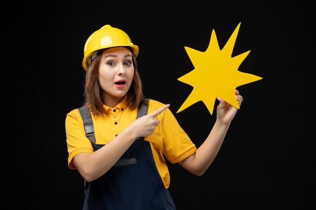 Widok z przodu kobieta budowlana w mundurze trzymająca żółtą postać na czarnej ścianie