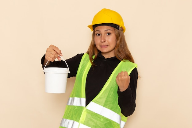 Widok z przodu kobieta budowniczy w żółtym kasku trzyma farbę na białej ścianie kobieta architekt budowy konstruktora