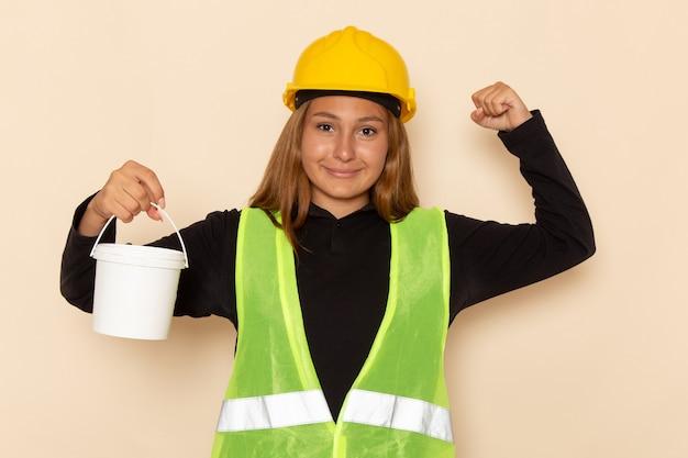 Widok z przodu kobieta budowniczy w żółtym kasku, trzymając farbę i zginanie na białej ścianie kobieta architekt budowy konstruktora