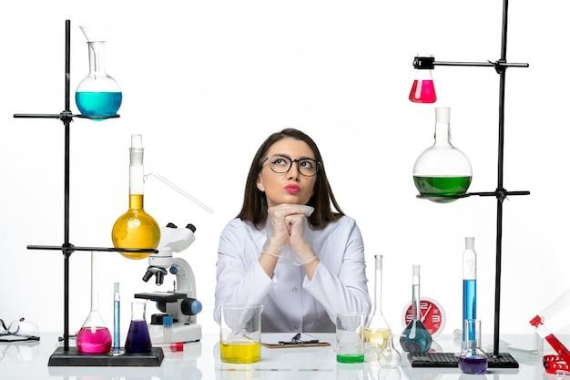 Widok z przodu kobieta chemik w białym garniturze medycznym, siedząca z roztworami, myśląca na białym tle science covid- lab pandemic virus
