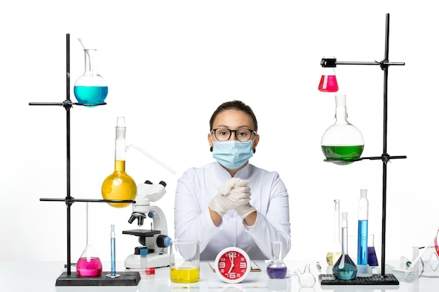 Widok z przodu kobieta chemik w białym garniturze medycznym z maską siedzi z roztworami na białym tle chemik virus covid splash lab