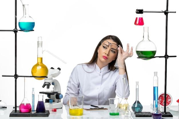 Widok z przodu kobieta chemik w białym kombinezonie medycznym przygotowuje się do pracy na białym tle laboratorium naukowe wirusa wirusa pandemii