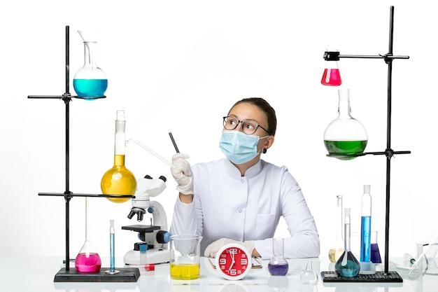 Widok z przodu kobieta chemik w białym kombinezonie medycznym z maską trzymającą pióro na jasnym białym tle chemik wirus covid-splash lab