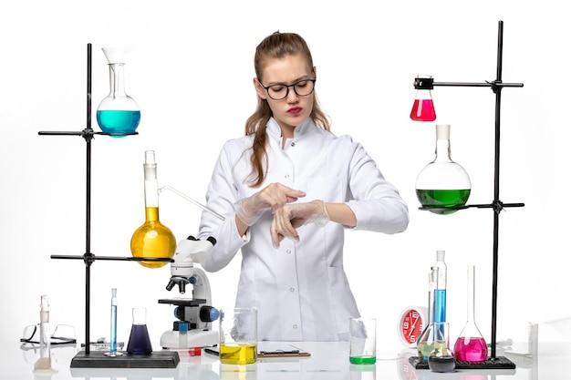 Widok z przodu kobieta chemik w garniturze medycznym, patrząc na jej nadgarstek na jasnym białym tle chemia pandemiczny wirus pandemiczny