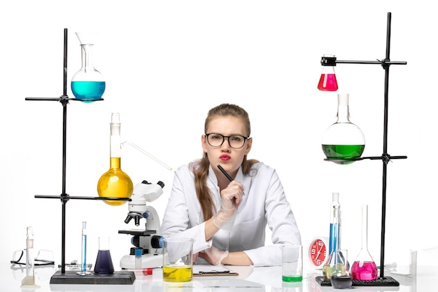 Widok z przodu kobieta chemik w garniturze medycznym, pisanie notatek na białym tle chemia pandemia zdrowia covid