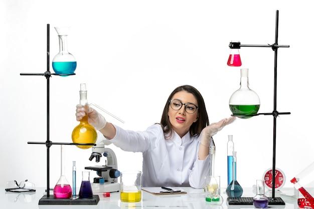 Widok z przodu kobieta chemik w garniturze medycznym siedząca wokół stołu z roztworami na jasnym białym tle wirus laboratoryjny pokrywający się nauką o pandemii