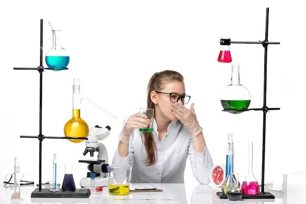 Widok z przodu kobieta chemik w garniturze medycznym sprawdzanie zapachu roztworu na białym tle chemia pandemia zdrowia covid