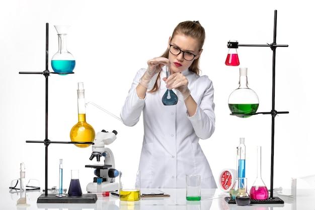 Widok z przodu kobieta chemik w garniturze medycznym w procesie pracy z roztworami na białym tle chemia pandemiczny wirus covid