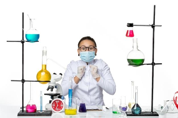 Widok z przodu kobieta chemik w garniturze medycznym z maską siedząca przed stołem z roztworami na jasnym białym tle laboratorium chemii wirusów covid splash