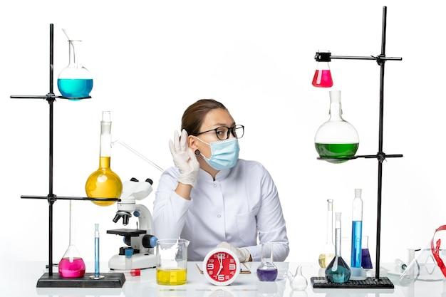 Widok Z Przodu Kobieta Chemik W Garniturze Medycznym Z Maską Siedząca Z Roztworami Próbująca Usłyszeć Na Białym Tle Wirus Laboratoryjny Chemika Covid- Plusk Darmowe Zdjęcia