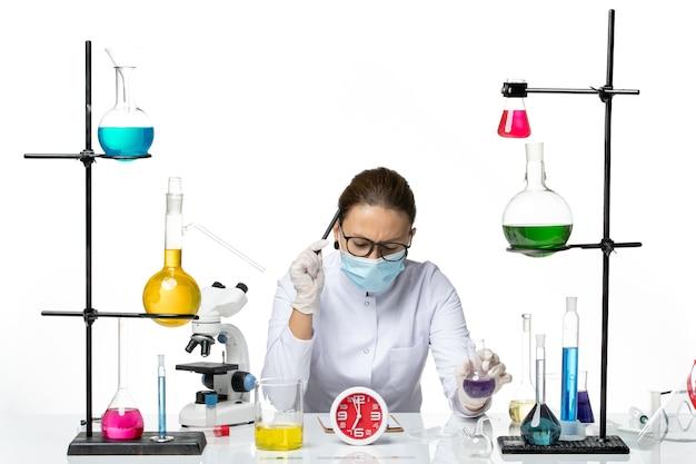 Widok z przodu kobieta chemik w garniturze medycznym z maską siedzącą z roztworami trzymającymi pióro i roztwór na białym tle plusk laboratorium wirus chemii covid
