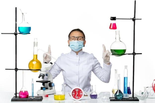 Widok z przodu kobieta chemik w garniturze medycznym z maską siedzi z roztworami modląc się na białym tle laboratorium wirusów chemia covid splash