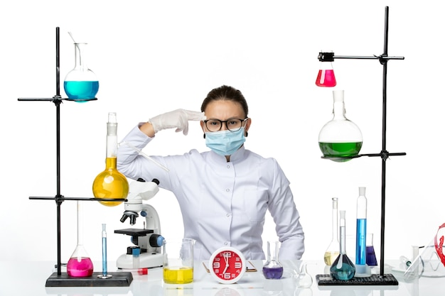 Widok z przodu kobieta chemik w garniturze medycznym z maską siedzi z roztworami na białym biurku laboratorium wirusów chemii covid- splash