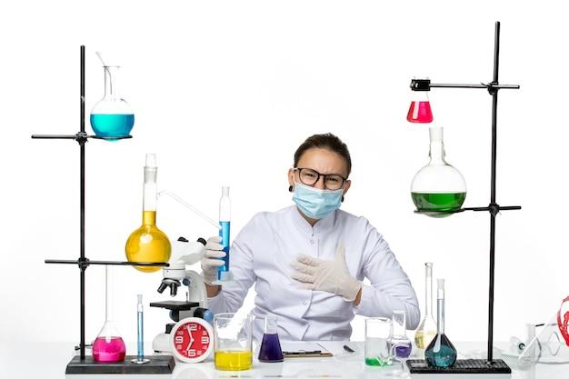 Widok z przodu kobieta chemik w garniturze medycznym z maską trzymając kolbę z niebieskim roztworem na białym tle plusk laboratorium chemii covid