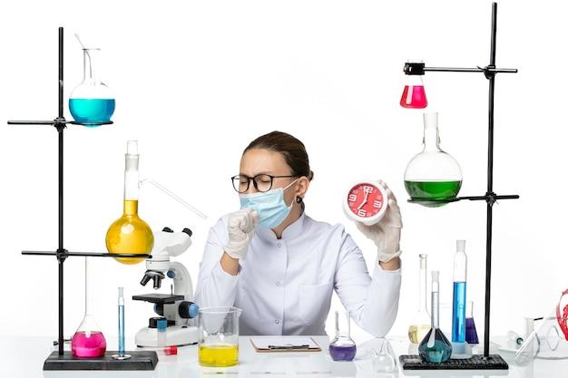 Widok z przodu kobieta chemik w garniturze medycznym z maską trzymającą czerwone zegary i kaszel na białym tle laboratorium wirusów chemia covid- plusk