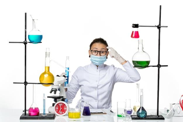 Widok z przodu kobieta chemik w garniturze medycznym z maską trzymającą kolbę z niebieskim roztworem na białym tle laboratorium chemii wirusa covid splash