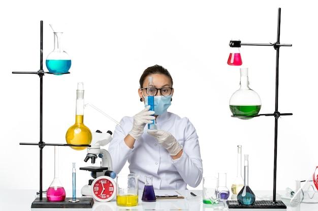 Widok z przodu kobieta chemik w garniturze medycznym z maską trzymającą kolbę z niebieskim roztworem na białym tle plusk wirus chemii laboratorium covid