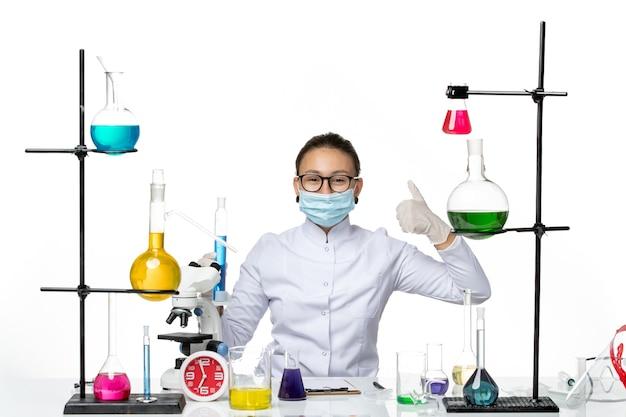 Widok z przodu kobieta chemik w garniturze medycznym z maską trzymającą kolbę z niebieskim roztworem uśmiechnięta na białym tle plusk wirus chemii laboratorium covid