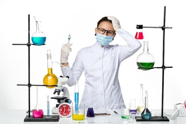 Widok z przodu kobieta chemik w garniturze medycznym z maską trzymającą zastrzyk na białym tle laboratorium chemii wirusa covid splash