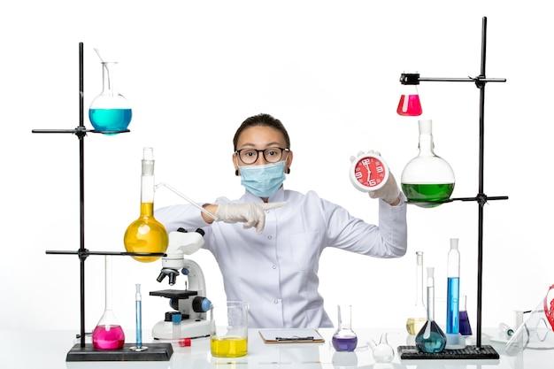 Widok z przodu kobieta chemik w garniturze medycznym z maską trzymającą zegary na jasnym białym tle laboratorium wirusów chemia covid splash
